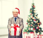 Homme de sourire dans le costume et chapeau d'aide de Santa avec le cadeau Photos stock