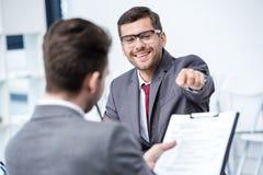 Homme de sourire dans le costume et lunettes se dirigeant au presse-papiers à l'entrevue d'emploi Image libre de droits