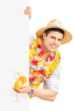 Homme de sourire dans le costume traditionnel derrière une exploitation de panneau vide Photo stock