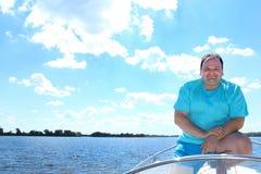 Homme de sourire dans un bateau sur un fond de l'eau lisse d'un ciel nuageux bleu photographie stock