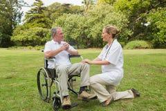 Homme de sourire dans un fauteuil roulant parlant avec son infirmière se mettant à genoux à coté Image libre de droits