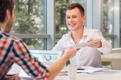 Homme de sourire donnant le dossier à son collègue Image stock