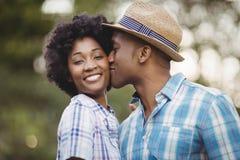 Homme de sourire embrassant sa joue d'amies Photo stock