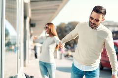 Homme de sourire essayant d'écarter son amie de magasin Photographie stock libre de droits