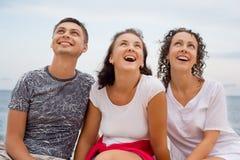 Homme de sourire et deux jeunes femmes s'asseyant sur la plage Photographie stock
