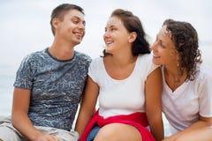 Homme de sourire et deux jeunes femmes s'asseyant sur la plage Images libres de droits