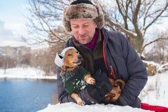 Homme de sourire et petit chien, portant dans des chapeaux drôles d'un hiver Photos libres de droits