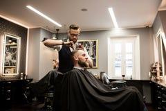 Homme de sourire faisant couper des cheveux dans le salon photographie stock