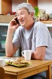 Homme de sourire faisant l'appel dans le café Photos stock