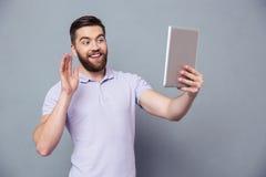 Homme de sourire faisant le faire appel visuel à la tablette Images libres de droits