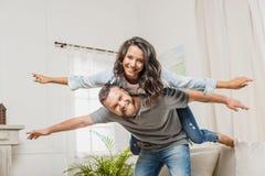 Homme de sourire ferroutant son amie attirante à la maison Photo libre de droits