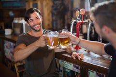 Homme de sourire grillant la tasse de bière avec l'ami masculin Photo stock