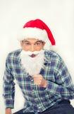 Homme de sourire heureux avec la chemise et le chapeau rouge de Noël feignant à Photos stock