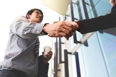 Homme de sourire heureux d'affaires se serrant la main après un finissage d'affaire photographie stock