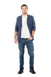 Homme de sourire heureux dans les jeans et la chemise de denim avec la main dans la poche regardant l'appareil-photo Photographie stock libre de droits