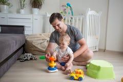 Homme de sourire heureux enseignant à son bébé garçon comment construire la tour de jouet Photo stock