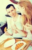 Homme de sourire heureux et amie positive avec le petit déjeuner savoureux Photographie stock libre de droits