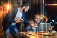 Homme de sourire indiquant l'ordinateur portable et la position à côté de son ami Image libre de droits