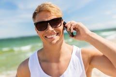 Homme de sourire invitant le smartphone sur la plage d'été Images stock