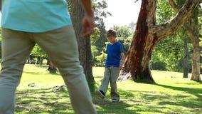 Homme de sourire jouant avec du ballon de football avec son fils clips vidéos