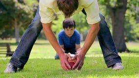 Homme de sourire jouant le rugby avec son fils banque de vidéos