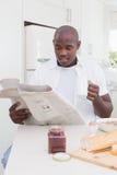 Homme de sourire lisant un journal et prendre son petit déjeuner photo libre de droits