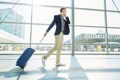 Homme de sourire marchant dans la station avec le téléphone et la valise Images stock