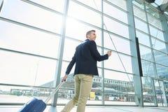 Homme de sourire marchant dans la station avec le téléphone et la valise Photographie stock libre de droits