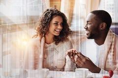 Homme de sourire mettant un anneau de mariage sur le doigt de sa femme Photo libre de droits