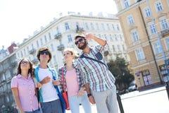 Homme de sourire montrant quelque chose aux amis sur la rue de ville Image stock