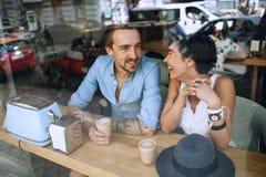 Homme de sourire parlant à la femme en café Photos stock