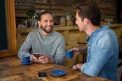Homme de sourire parlant avec l'ami à la table dans le café Photo libre de droits