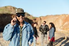 Homme de sourire parlant par le téléphone marchant à la plage avec des amis Images libres de droits