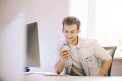 Homme de sourire parlant sur le téléphone portable tout en à l'aide de l'ordinateur portable au bureau dans l'étude Photos stock