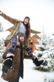 Homme de sourire portant son amie sur des épaules en hiver Photo libre de droits