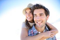 Homme de sourire portant son amie sur la plage Photos stock