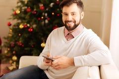 Homme de sourire posant sur le sofa avec le téléphone dans des mains Image stock
