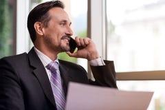 Homme de sourire positif parlant au téléphone portable Photographie stock libre de droits