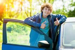 Homme de sourire près de voiture bleue Image stock