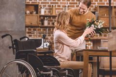 homme de sourire présent des fleurs à l'épouse handicapée image libre de droits