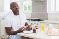 Homme de sourire prenant son petit déjeuner Images stock