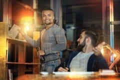Homme de sourire prenant un livre de l'étagère tandis que son ami le regardant Photographie stock libre de droits