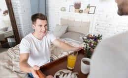 Homme de sourire recevant le petit déjeuner de son ami réfléchi Photographie stock