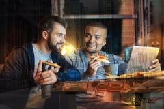 Homme de sourire regardant son ami tout en mangeant de la pizza avec lui Image libre de droits