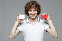 Homme de sourire retenant des cartes de crédit en blanc Image libre de droits
