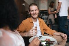 Homme de sourire s'asseyant dans le restaurant et parlant avec la fille Garçon s'asseyant au café avec le verre de l'eau à dispos Photos stock