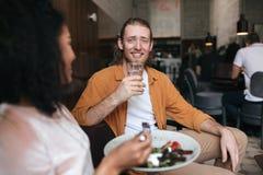 Homme de sourire s'asseyant dans le restaurant et parlant avec la fille Garçon s'asseyant au café avec le verre de l'eau à dispos Photos libres de droits