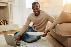 Homme de sourire s'asseyant sur le plancher avec le papier Photographie stock libre de droits