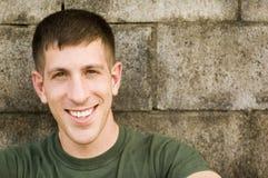 Homme de sourire se penchant sur le mur Photographie stock libre de droits