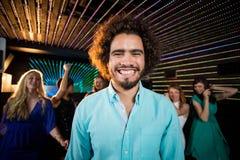 Homme de sourire se tenant dans la piste de danse Image stock